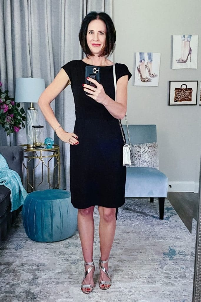 April from Stunning Style wearing a black dress with black with silver heels and a matching silver bag.