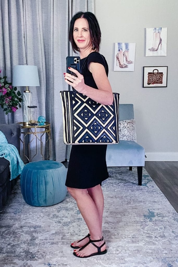 April from Stunning Style wearing a ligh dress with black flats and a straw and leather bag.