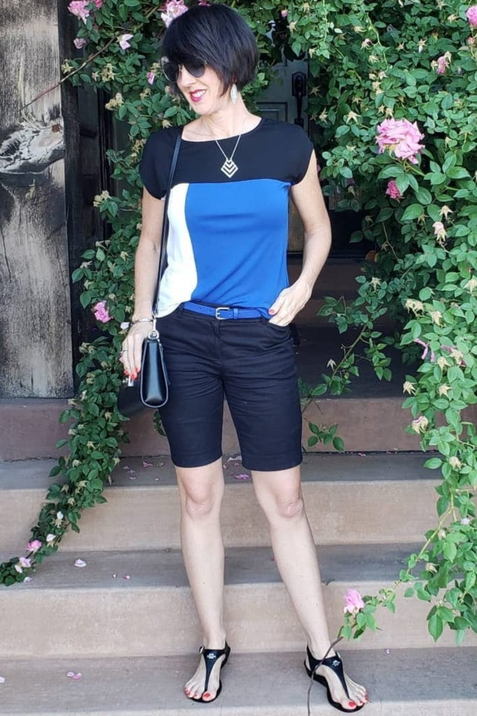 April from Stunning Style wearing a color blocked top with dark Bermuda shorts.
