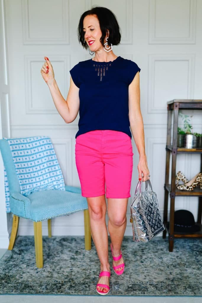 April from Stunning Style wearing a navy top with pink Bermuda shorts.