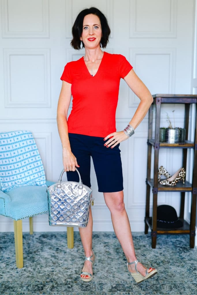 April from Stunning Style wearing a red top with dark Bermuda shorts.