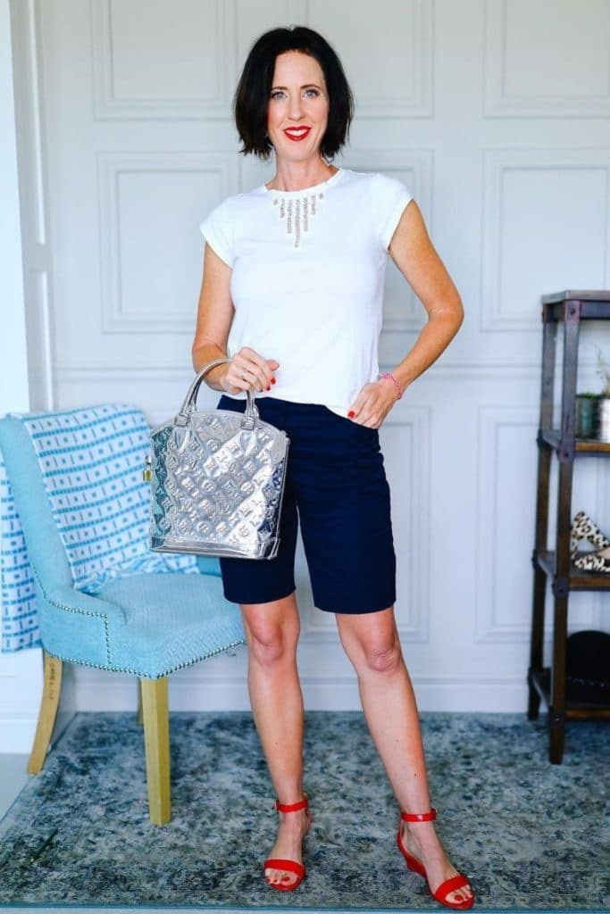April from Stunning Style wearing a white top with black chino style Bermuda shorts.