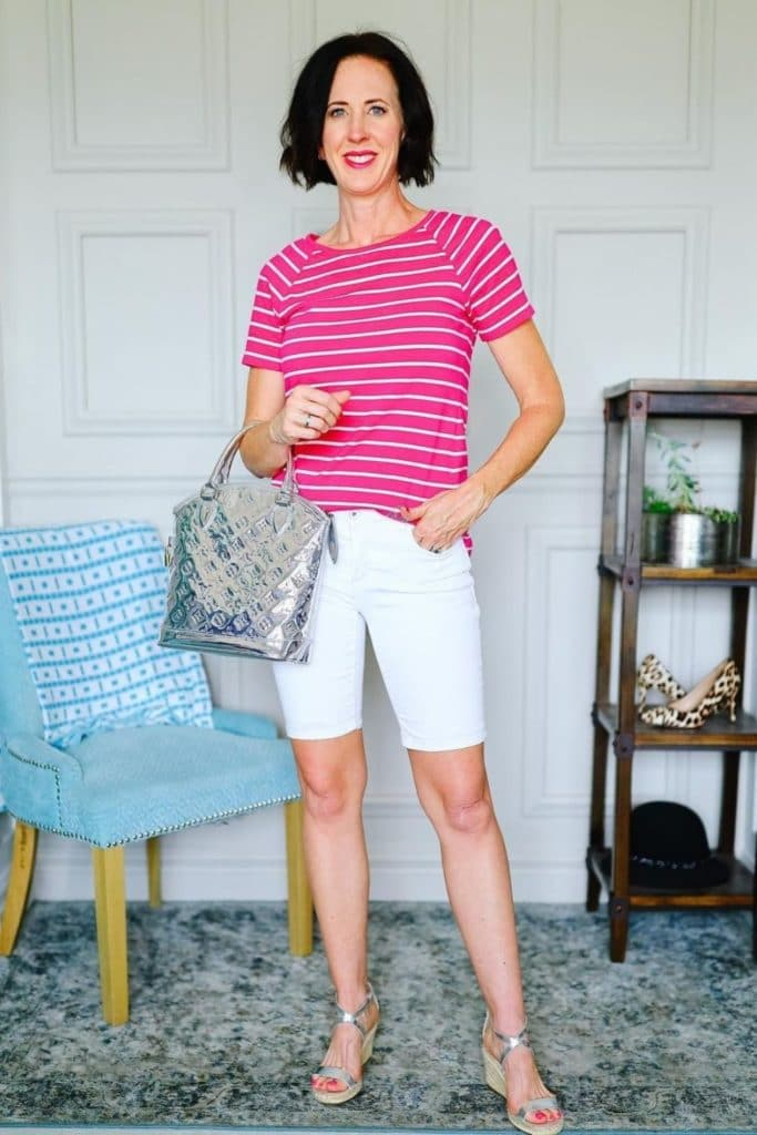April from Stunning Style wearing a pink striped top with white chino style Bermuda shorts.